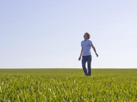 jongen tiener lopen op een veld bedekt met groene scheuten tarwe