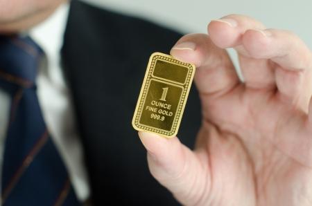 lingotes de oro: Barra de oro en manos de un hombre de negocios Foto de archivo