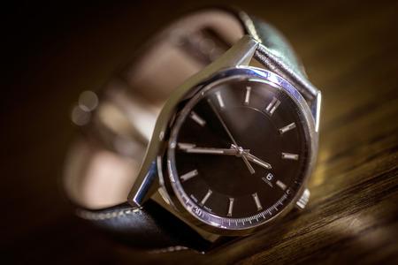블랙 다이얼과 가죽 시계 밴드가있는 고급 시계.
