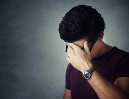 Young Man Covering His Face Looking Down Stock Photo