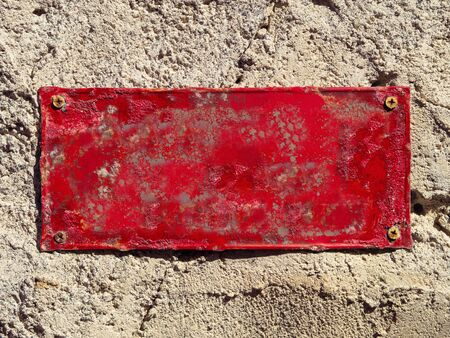 Rusty Red Painted Empty Metal Sign Plate Screwed on a Wall