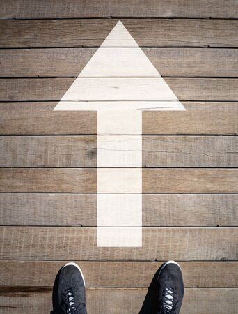 One Way Going Forward. Big White Arrow Pointing Straight Ahead on Wooden Floor in Front of Two Feet in Shoes. Moving On Concept.
