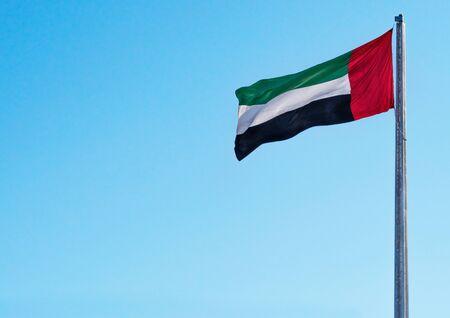 UAE National Flag of United Arab Emirates Waving on Sunny Blue Sky Clean Background Stock Photo