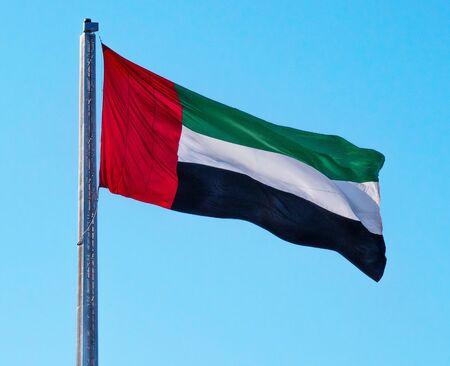 UAE National Flag of United Arab Emirates Waving on Sunny Blue Sky Clean Background 版權商用圖片