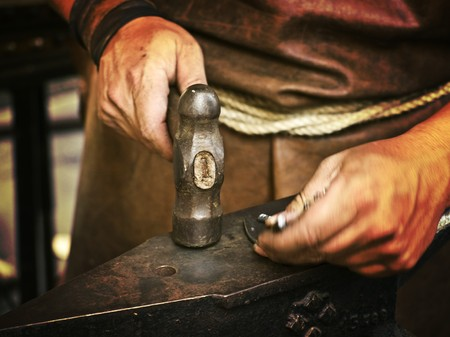 The overworked hands of a medieval blacksmith giving shape a