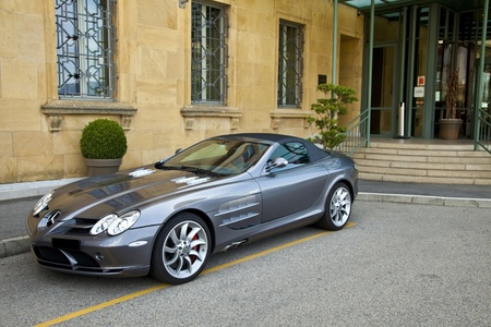 Neuchatel, Switzerland - August 10, 2011: Silver Mercedes McLaren SLR parked at the entrance of Hotel Beau-Rivage in Neuchatel, Switzerland. This anglo-German sports car is developed by Mercedes-Benz and McLaren Automotive. Editorial