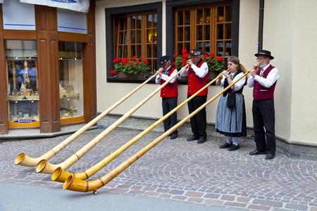 alphorn: Band of swiss musicians playing in Zermatt streets