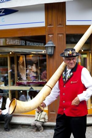 zermatt: Swiss musician with a typical Alphorn