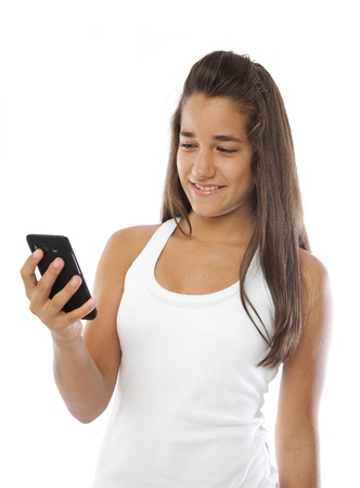 Cute teenager smiling with a mobile phone isolated on white photo
