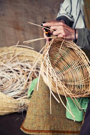 hand basket: Older hands making a wicker basket