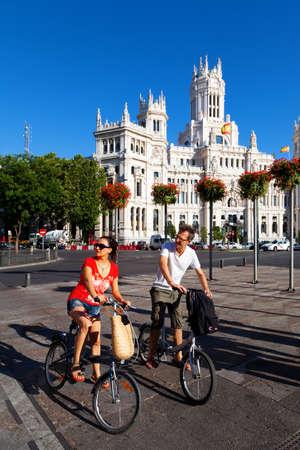 palacio de comunicaciones: Tourists visiting Madrid on bicycle Editorial