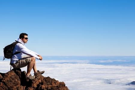 Junger Mann mit einem Rest in einem High Peak über Wolken in Berg Teide Standard-Bild