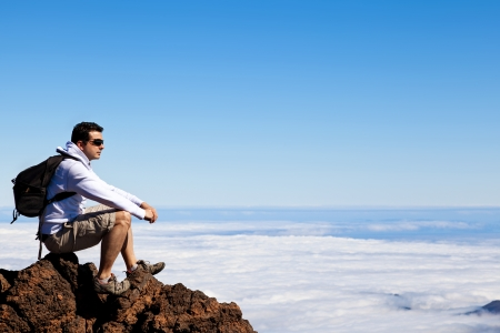Young Man Having a Rest in a High Peak Over Clouds in Teide Mountain photo