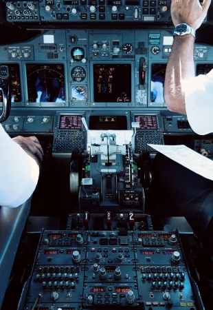 pilot cockpit: Airliner Cockpit with Pilots Working Editorial
