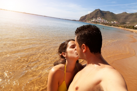 Young Couple Kissing in Las Teresitas Beach, Tenerife photo