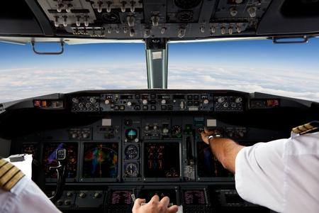 piloto: Los pilotos que trabajan en un avión durante un vuelo comercial Editorial