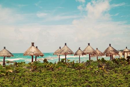 mayan riviera: Palapa sun roof beach umbrellas in Caribbean Sea, Mayan Riviera, Mexico Stock Photo