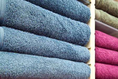 Piles of Multicolored Towels on a Wooden Shelves Stock Photo - 17984070
