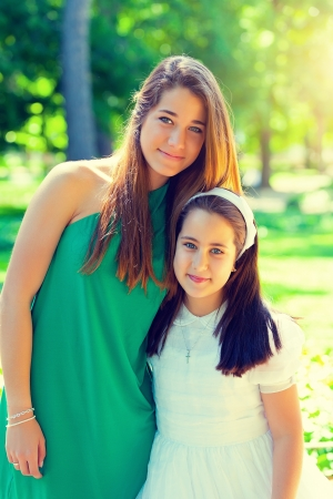 first day: Two beautiful sisters in the First Communion Day Stock Photo
