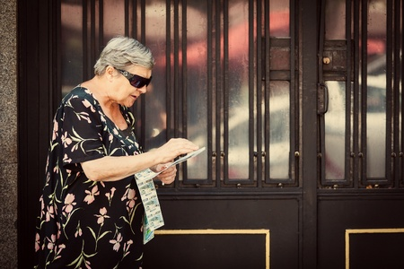 visually: MADRID, SPAIN - AUGUST 12: Senior Woman Selling ONCE Lottery Coupons in the Streets of Madrid. ONCE is a social and democratic non-profit entity that has the primary purpose of improving the quality of life for the blind and visually impaired of Spain. Editorial