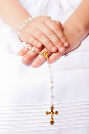 Hands of a little her in the First Communion Day Holding a Golden Cross photo
