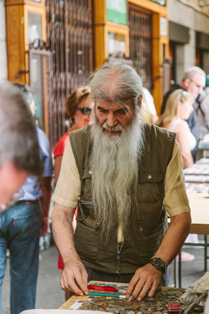 MADRID, SPAIN - SEPTEMBER 7: People at the Collectible Market of Stamps and Coins in Plaza Mayor, one of the most traditional Madrid classics on September 7, 2014 in Madrid.
