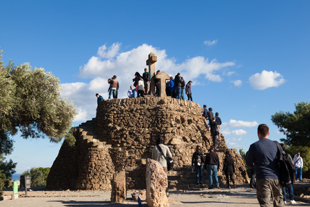 gazer: BARCELONA, SPAIN - NOVEMBER 15: Tourists in the Turó de Les Tres Creus where Gaudí wanted to finish his work from Park Guell. Built with prehistoric remains found at the site, on Noviember 15, 2014 in Barcelona, Spain Editorial