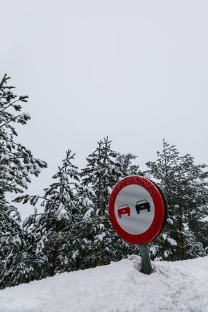overtake: No Overtaking Sign in a Snowy Road Stock Photo