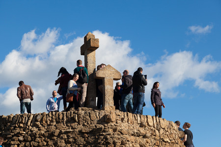 tres: BARCELONA, SPAIN - NOVEMBER 15: Tourists in the Turó de Les Tres Creus where Gaudí wanted to finish his work from Park Guell. Built with prehistoric remains found at the site, on Noviember 15, 2014 in Barcelona, Spain Editorial