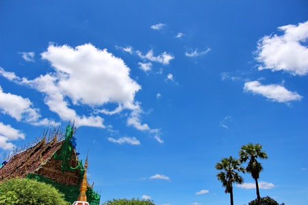 Thai Buddhist church under renovation with blue sky background