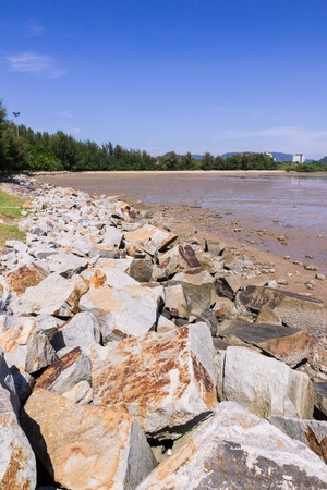 Rock for soil protection when low tide with blue sky background photo
