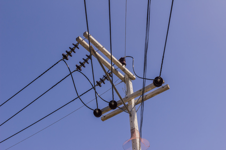 wire mess: Electrical post with electrical cables against blue sky background Stock Photo