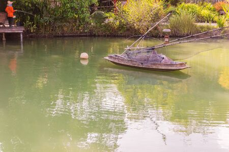 basketry: Thai wooden boat with fishing basketry float in garden