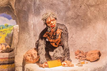 hombre prehistorico: Phuket, Tailandia - 26 de marzo, 2016: Escultura del hombre prehistórico en cueva demostró en el Museo de la Minería de Phuket, Tailandia Editorial