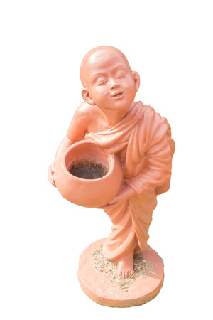 Buddhist novice holding alms bowl clay doll at Thai Buddhist temple, Phuket, Thailand