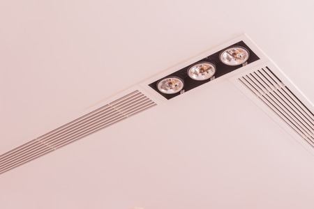 lighting fixtures: Construction details: Lighting fixtures and air grilles on plastered board ceiling Stock Photo