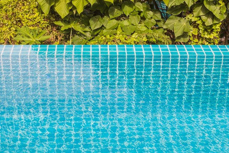 Swimming pool edge with garden background