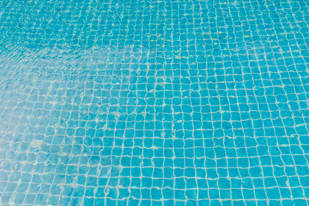 Swimming pool with turquoise blue tiles can be used us background