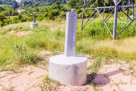 Construction details: Round stump concrete column with galvanized steel leg of the high voltage transmission tower, ready to continue erection its tower, Thailand Stock Photo