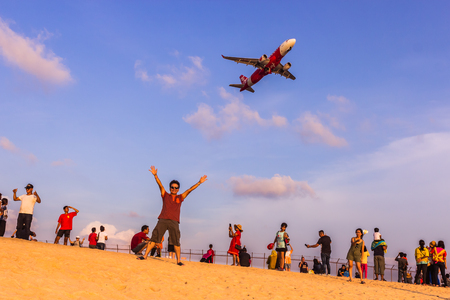 Phuket, Thailand - April 14, 2019: Tourists enjoy taking a picture with the airplane flying over them as the background, at the Mai Khao Beach, the edge of Phuket International Airport,Thailand
