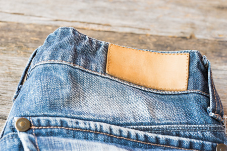 leather label: Blank leather label blue jeans on wooden background.