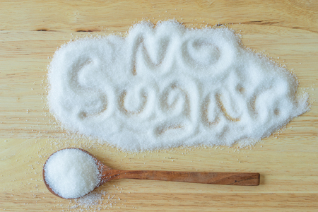 granulated: Inscription sugar made into pile of white granulated sugar on wooden  background.