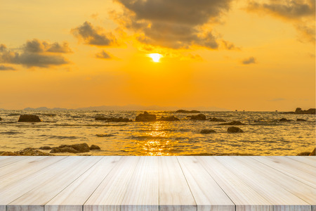 Empty wooden table or shelf wall with  sunset or sunrise on sand beach background. For present your products. Stock Photo