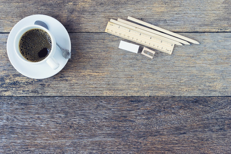 Black coffee in white Ceramic Cup and pencils on old wooden table.