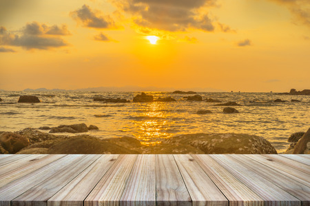 Empty wooden table or shelf wall with  sunset or sunrise on sand beach background. For present your products. Imagens