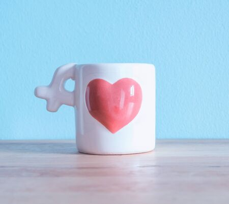 White Ceramic Coffee Cup with pink heart on the wooden tables and light blue walls. For you valentines background.