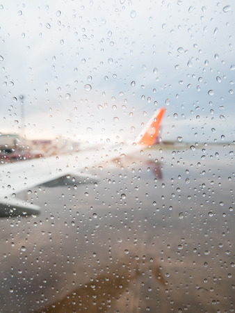 Abstract defocused blur of airplane at airport with sunset after the heavy rain. -Focus on raindrops windows glass.