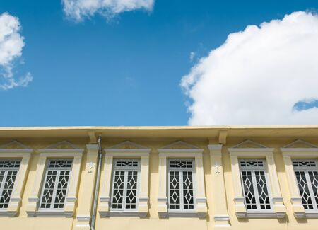 Old yellow building with blue sky and white clouds background. Imagens