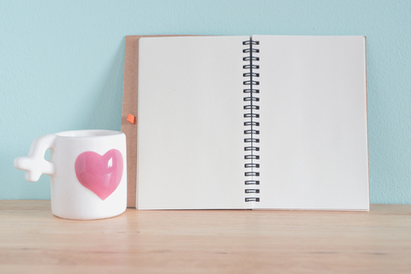 White Ceramic Coffee Cup with pink heart and Open Book on the wooden tables and light blue walls. For you valentines background.