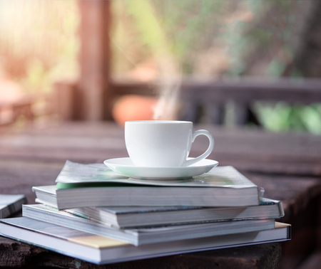 White ceramic coffee cup over the books on a wooden table in the garden with evening sunlight, -Lens flare filter.